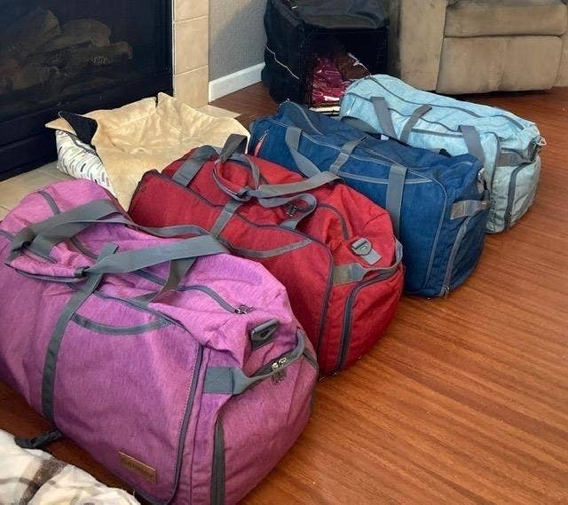A reviewer photo of four bags in pink, red, blue, and light blue next to each other