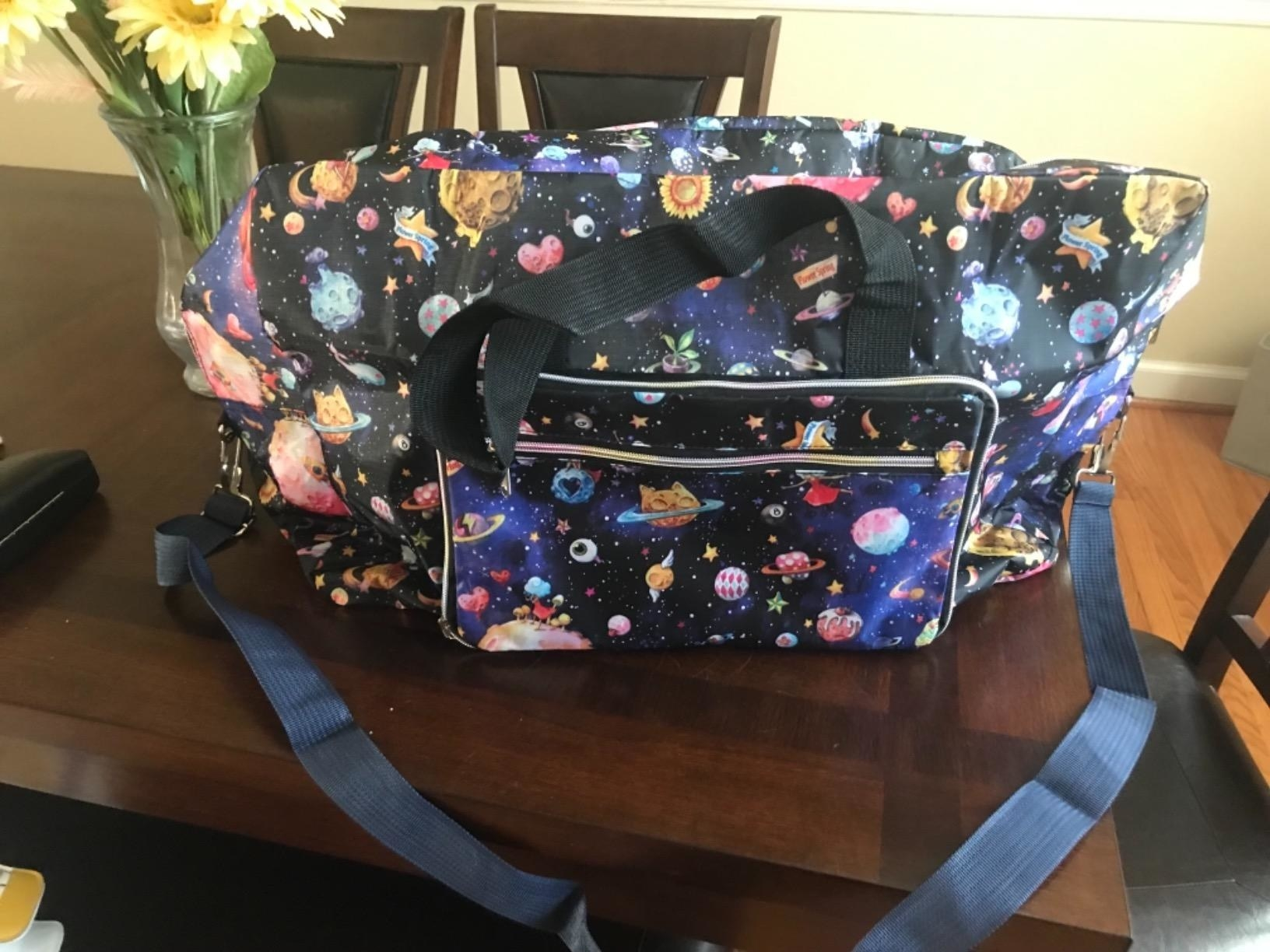 A reviewer photo of the duffel bag with a space and galaxy print all around it