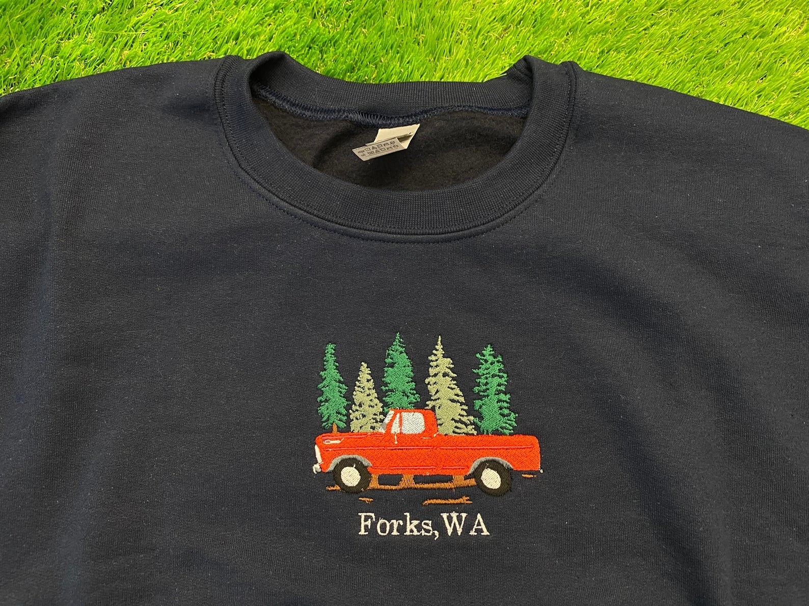 """black sweatshirt with red embroidered truck and trees behind it with """"Forks, WA"""" underneath"""