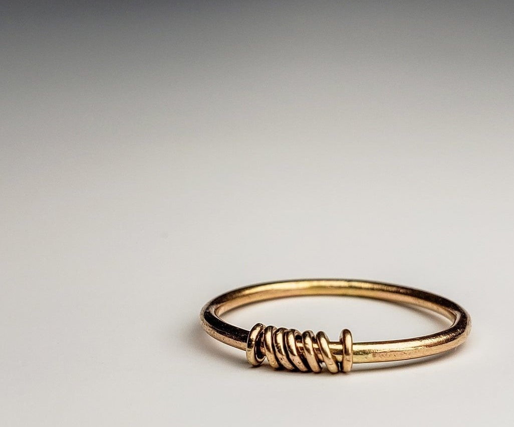 simple gold band with seven small round rings around it