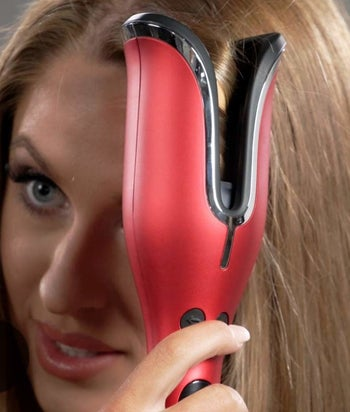 Model using curling iron on hair
