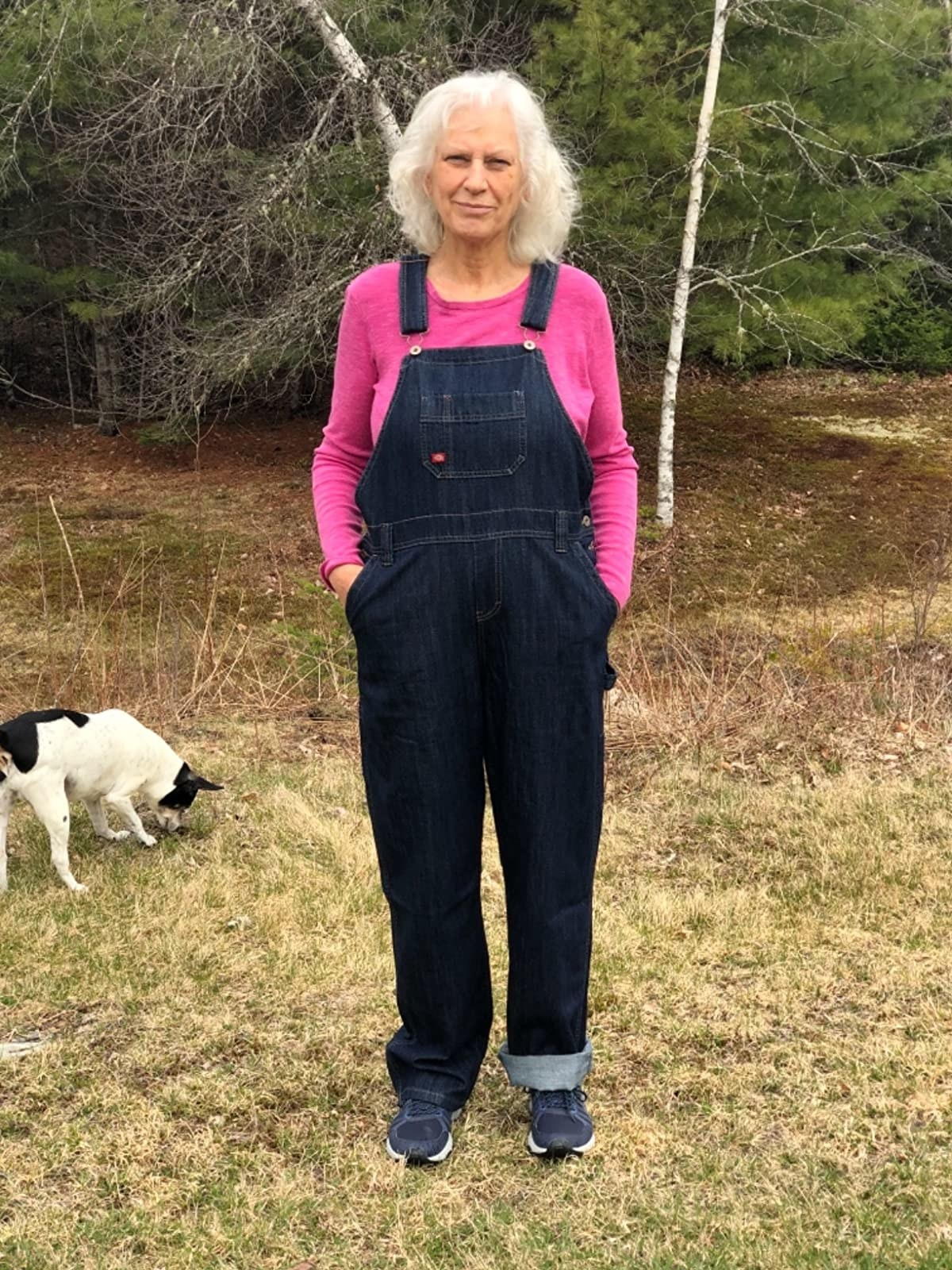 a reviewer wearing the dark indigo dickie's overalls outside