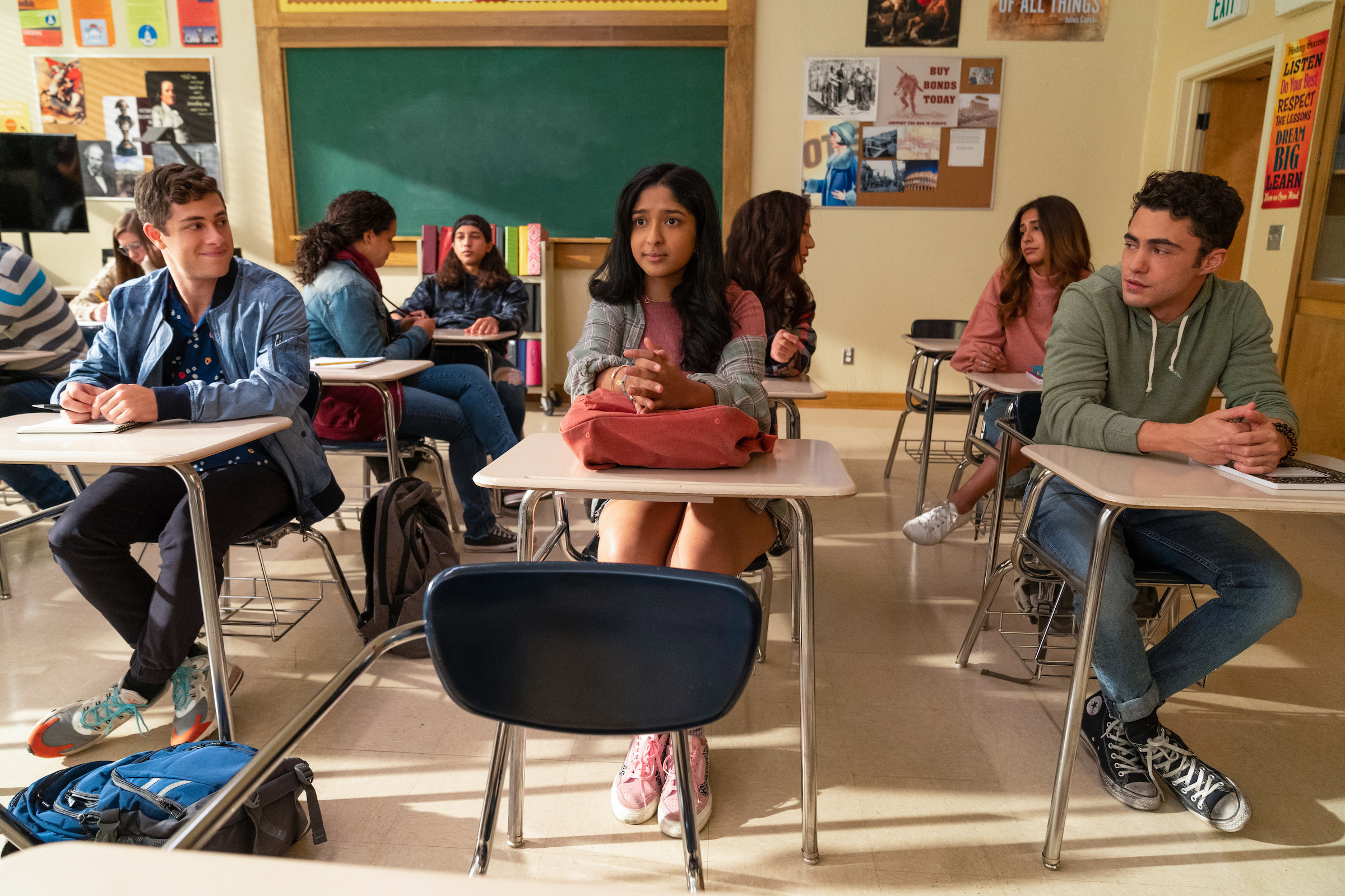 Devi sitting at her desk in class while her classmates sit around her