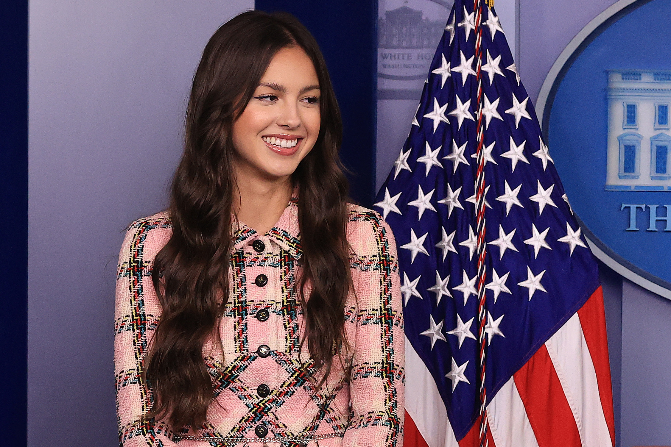Olivia Rodrigo smiles in front of the US flag