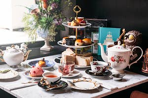 a full table set up for high tea with pastries and finger sandwiches