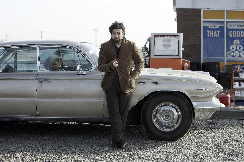 Oscar Isaac stands up against a car that Garrett Hedlund is in