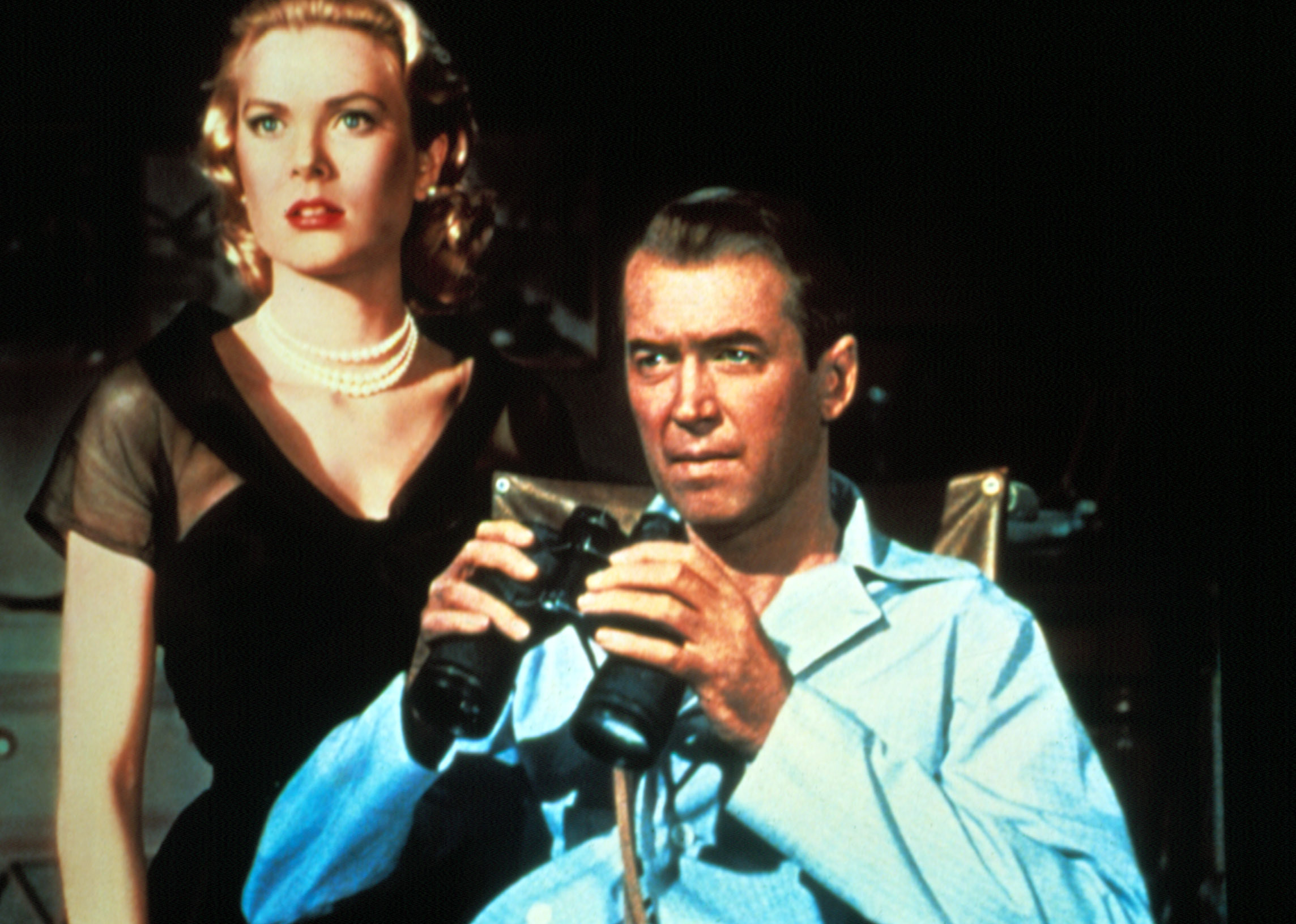 Grace Kelly and James Stewart look out a window with a pair of binoculars