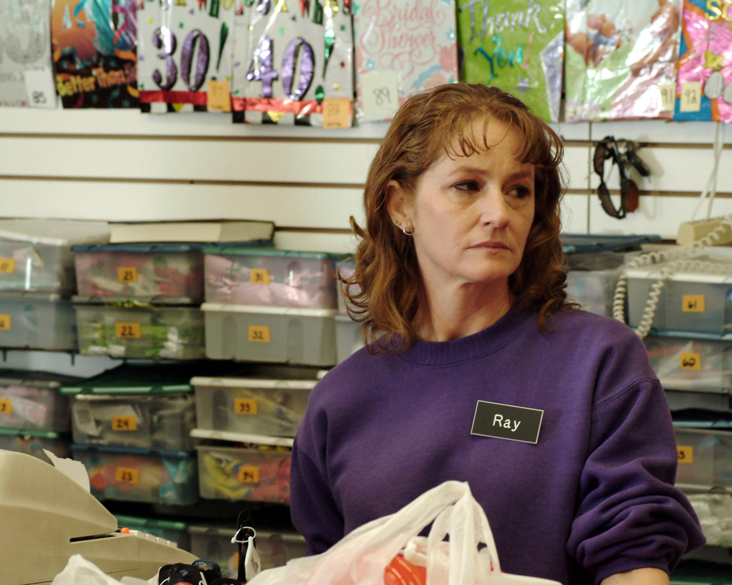 Melissa Leo stands behind a cash register