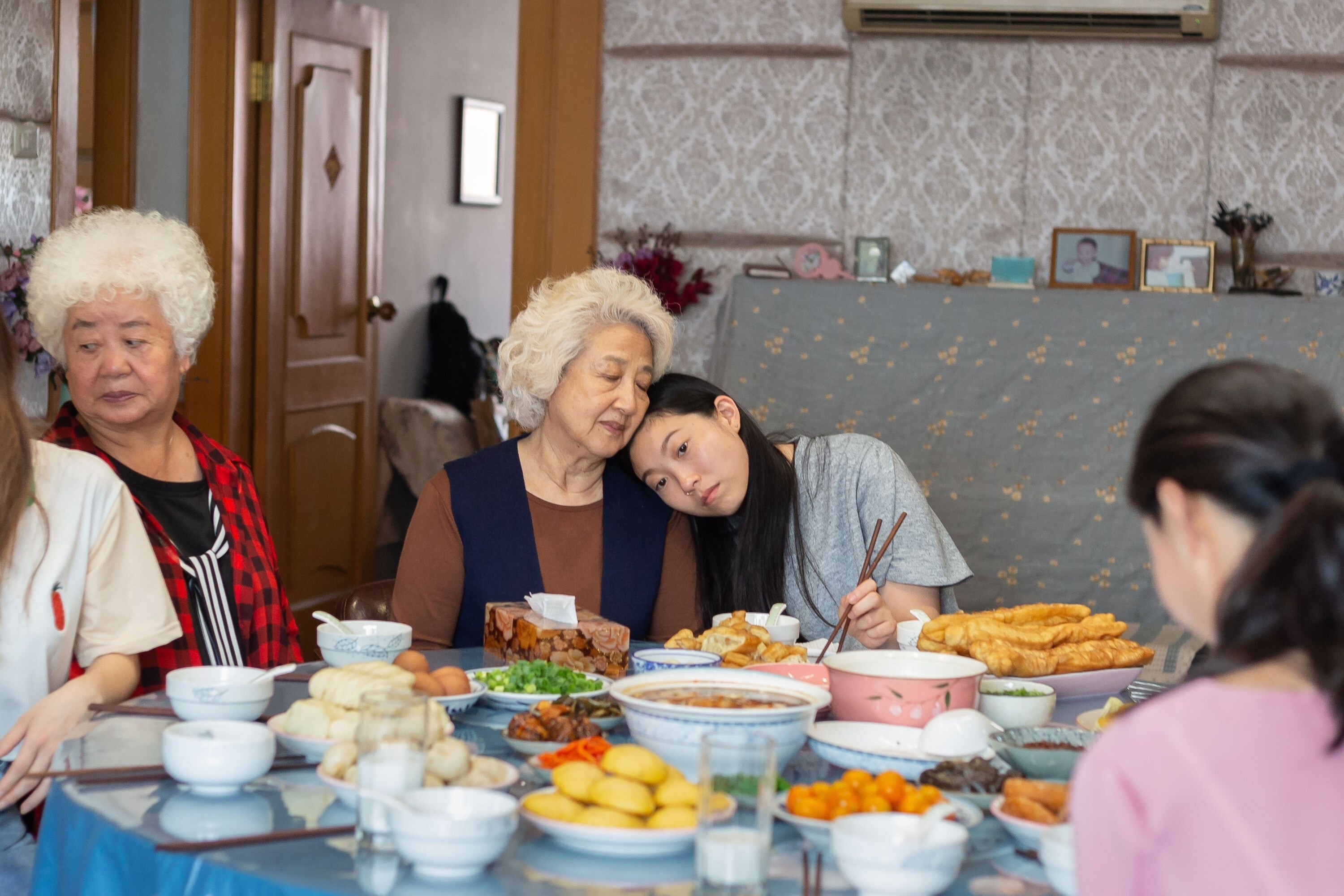 Awkwafina leens on Zhao Shuzhen's shoulder at the dinner table