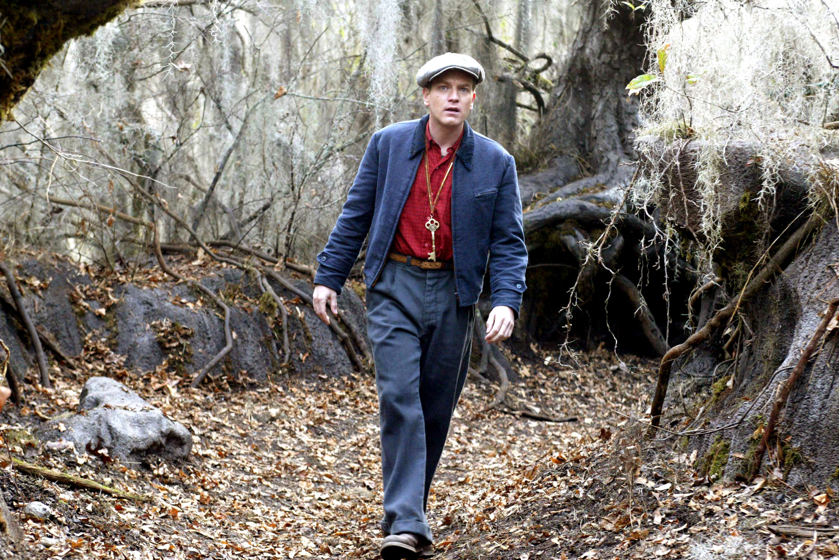 Ewan McGregor walking in the woods with a key around his neck