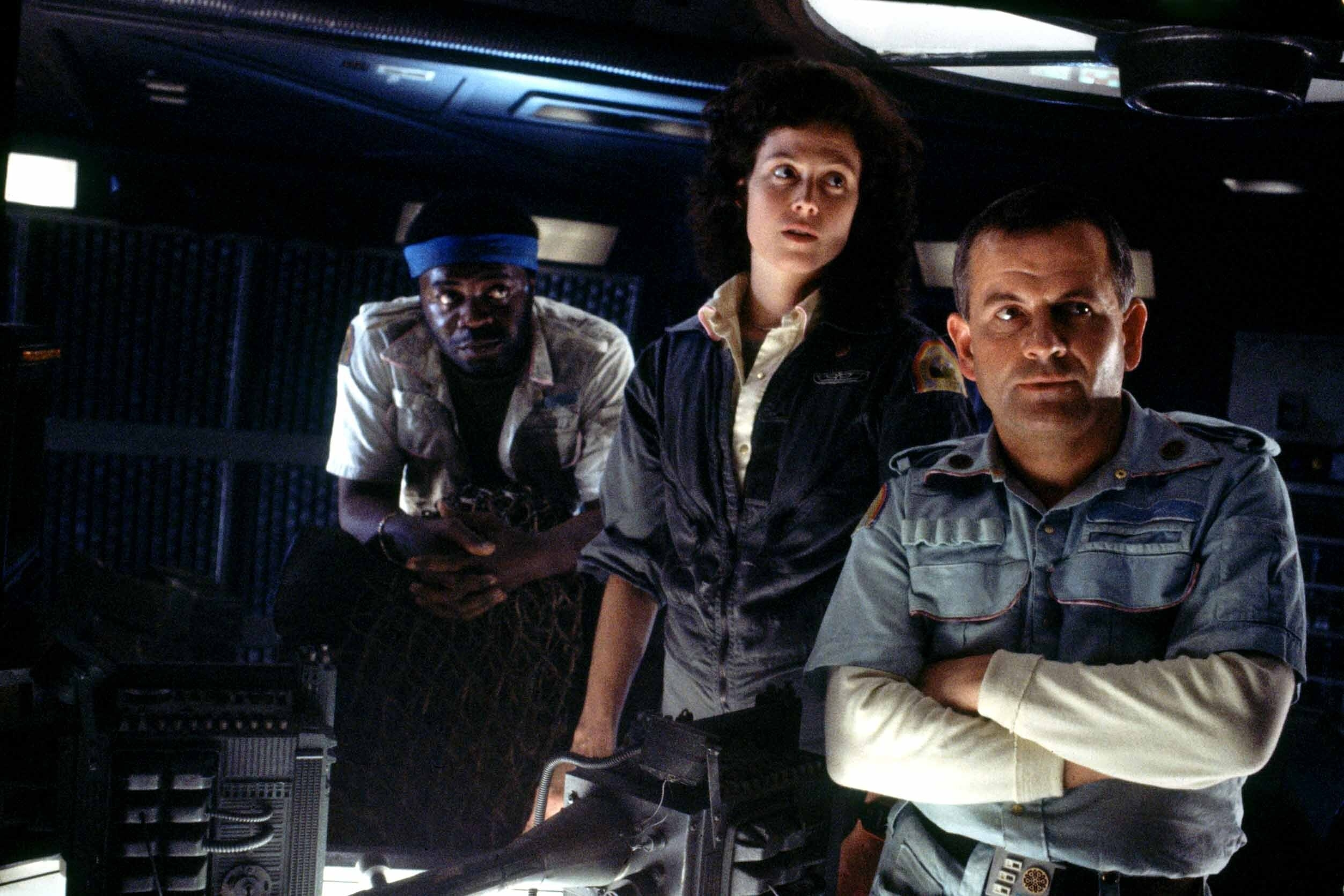 Yaphet Kotto, Sigourney Weaver, and Ian Holm stand in the control room of a space ship