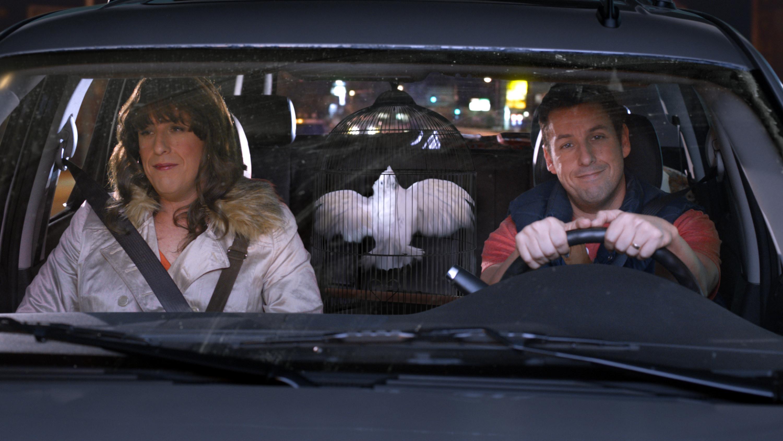 Adam Sandler, dressed as a woman, rides in a car with Adam Sandler dressed as a man