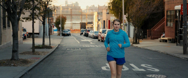 Jillian Bell runs down the street