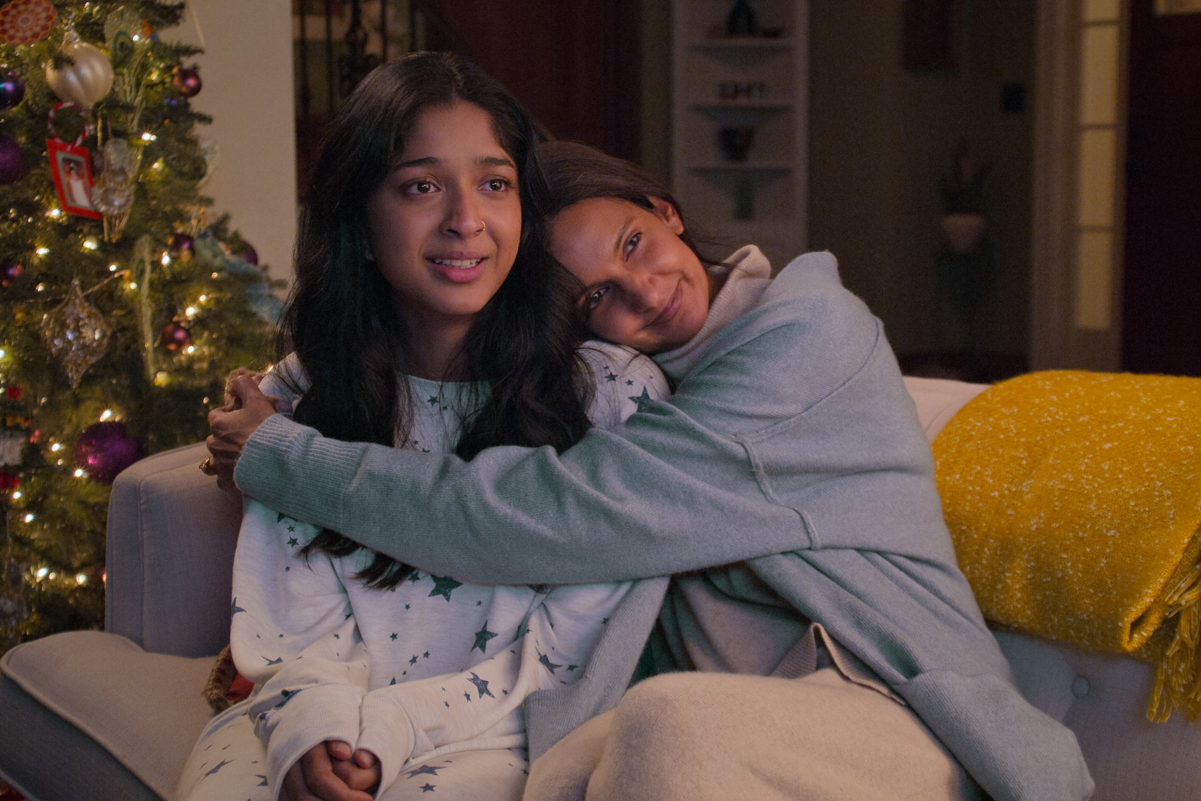 Devi being hugged on the couch with a Christmas tree in the background