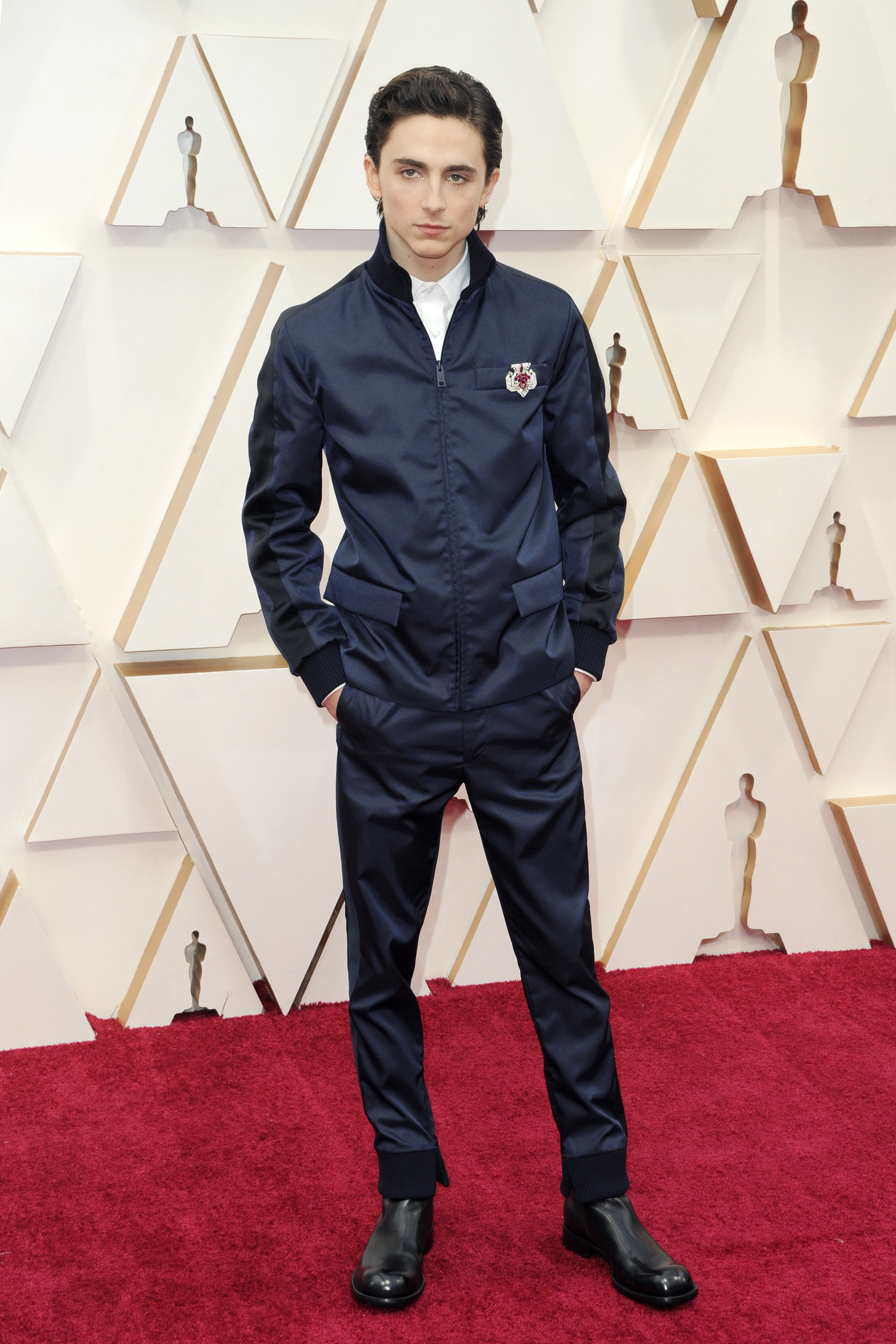 Timothée wears a navy nylon zip-up jacket and matching pants