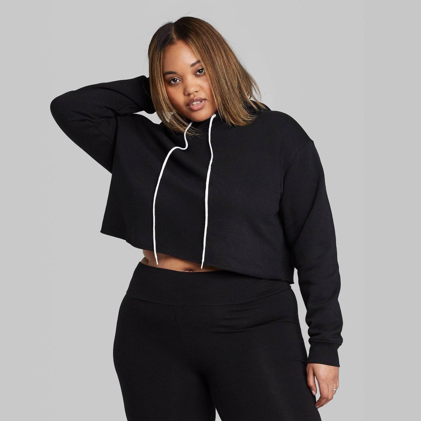 A model wearing a black cropped hoodie