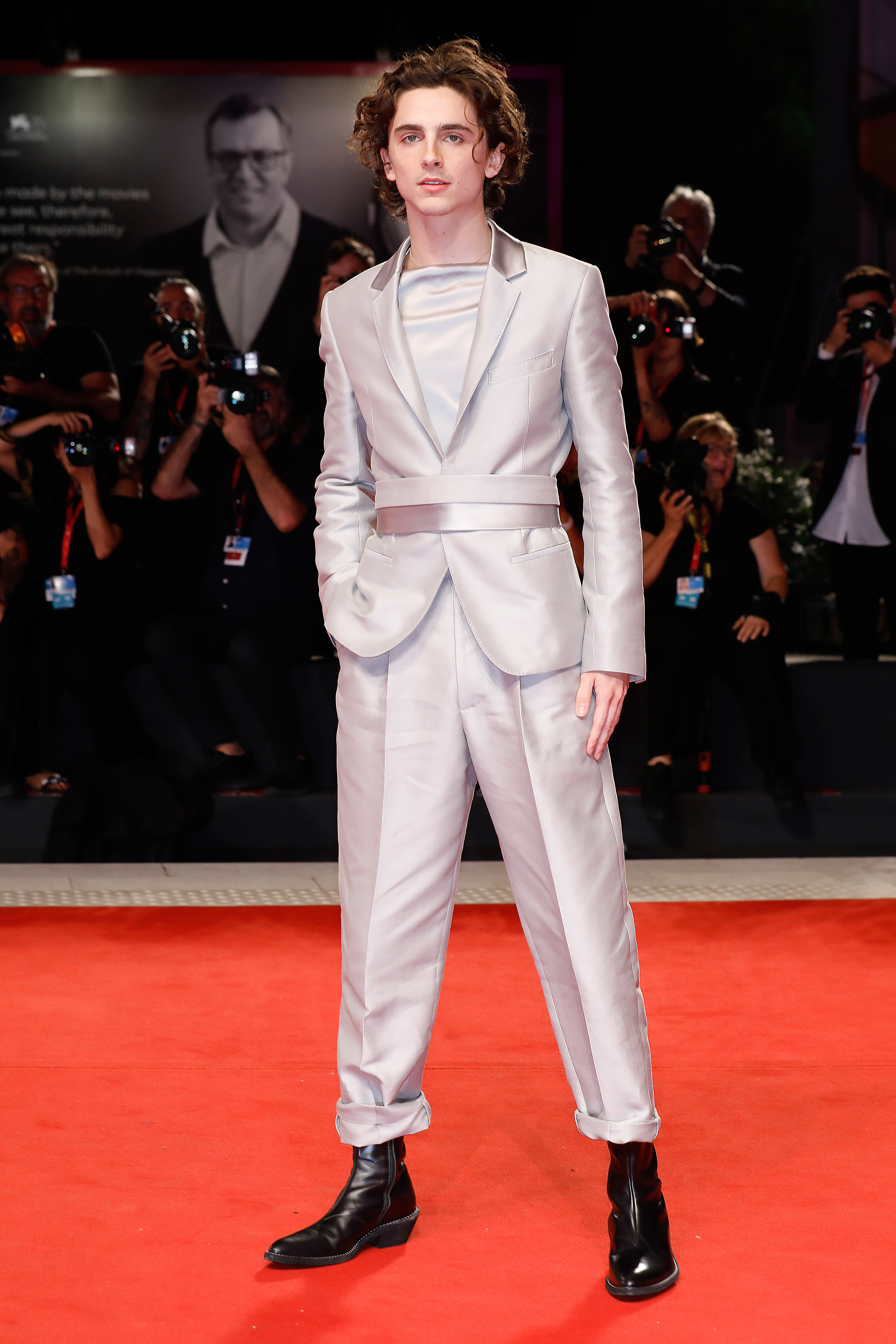 Timothée wears a grey suit with a silk waist band