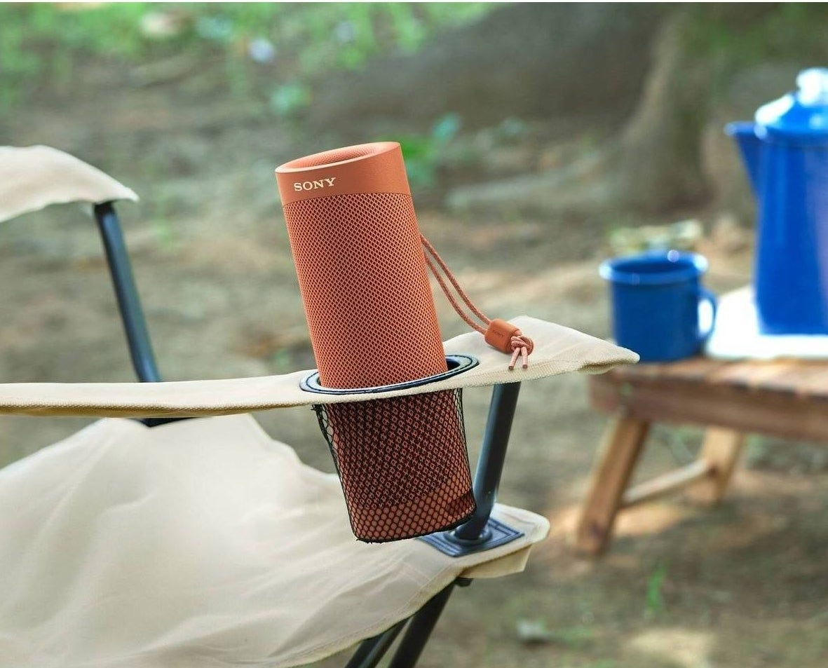an orange speaker resting in a fold out chair's cupholder