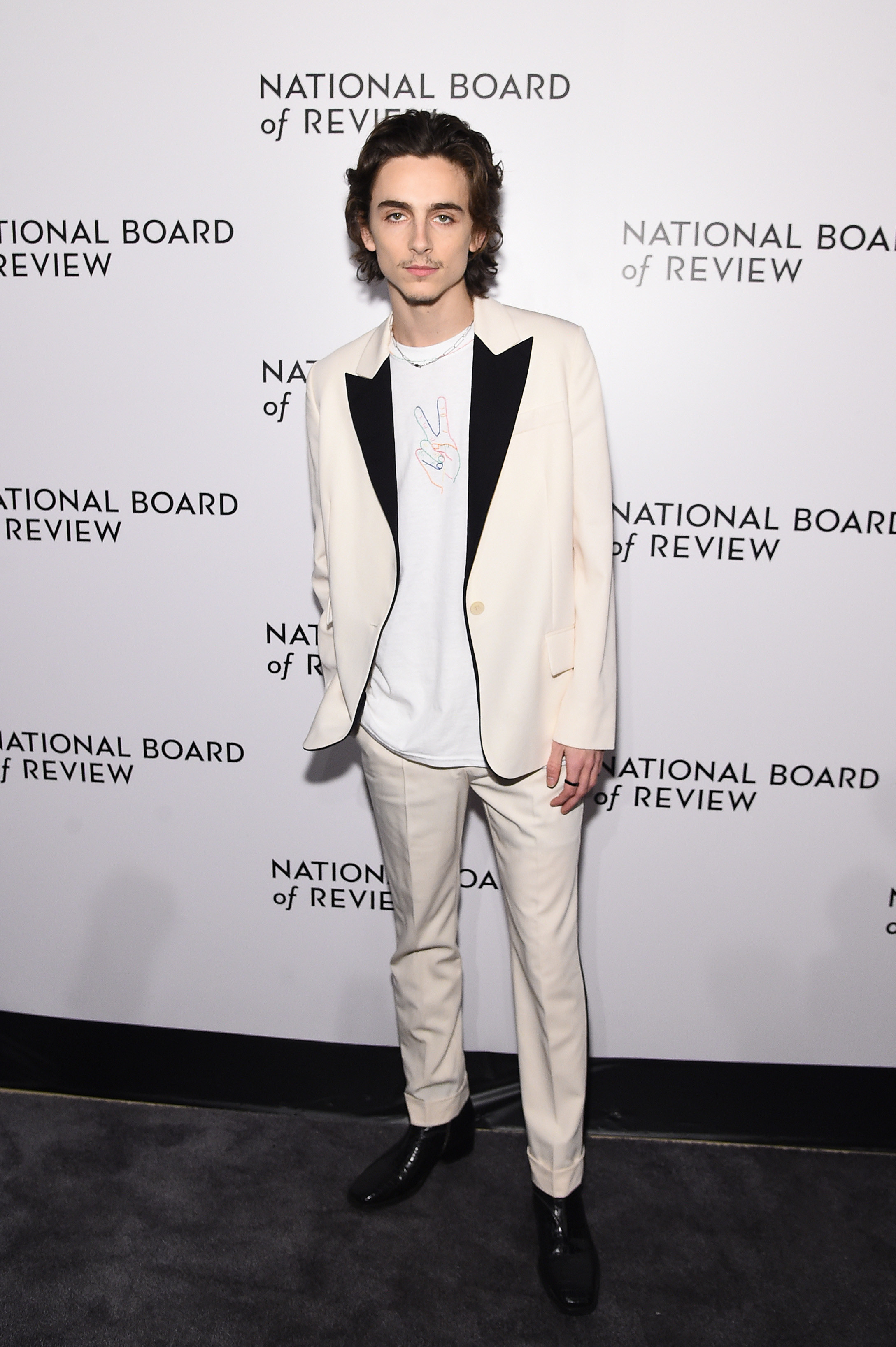 Timothée wears an ivory suit with a black lapel and white T-shirt