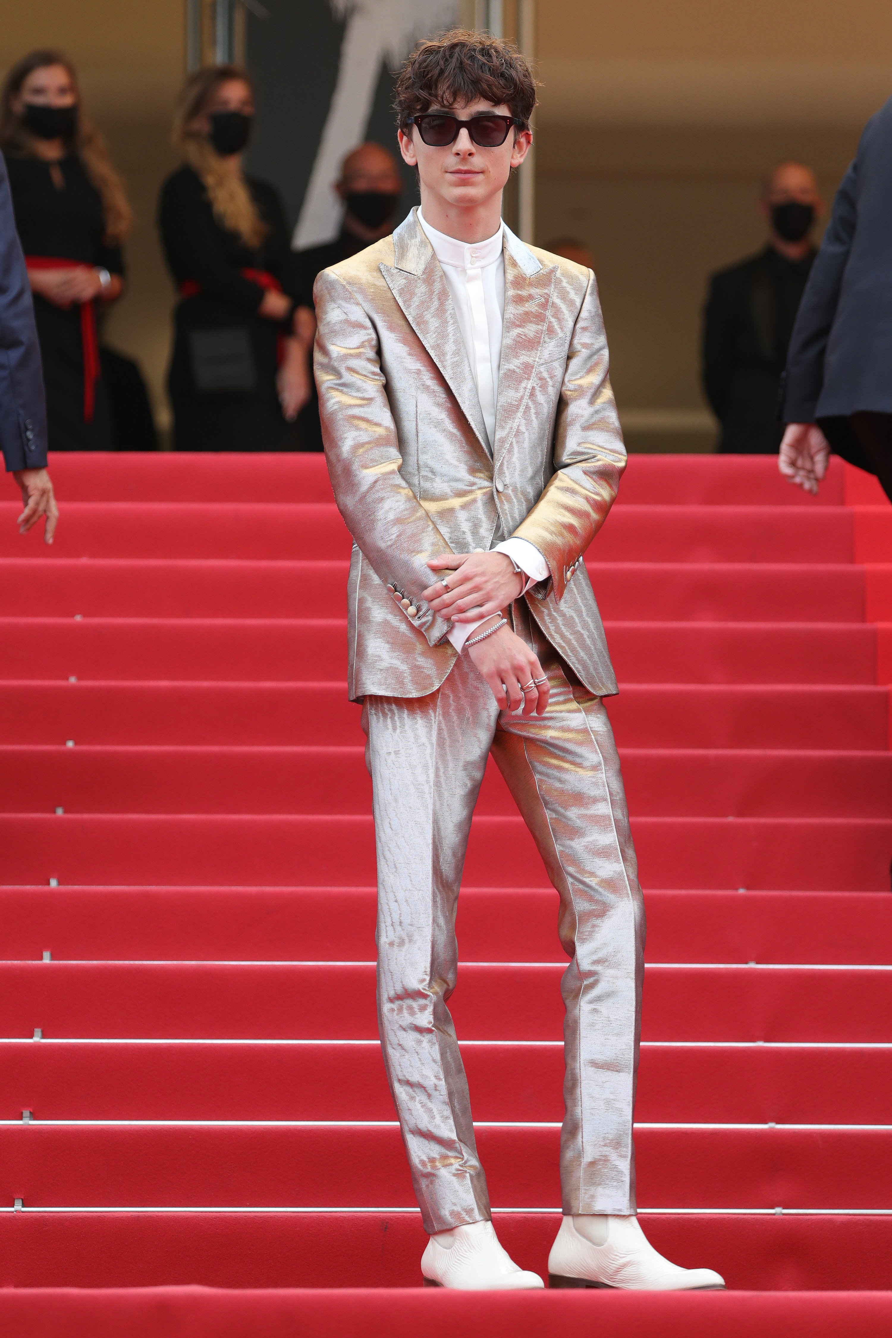Timothée wars a shimmering silver silk suit with white boots and sunglasses