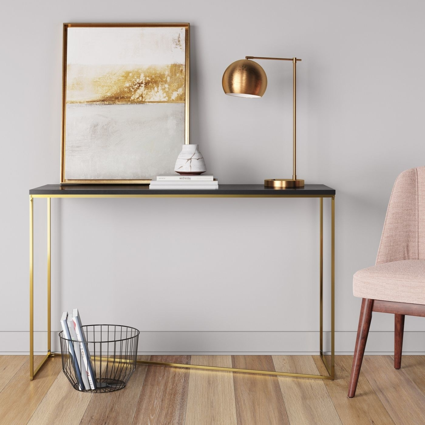 a console table with a gold asymmetrical base and a black top