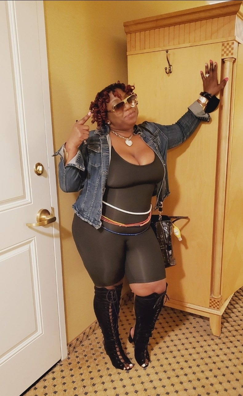 image of reviewer wearing the black body suit with thigh high boots and a denim jacket
