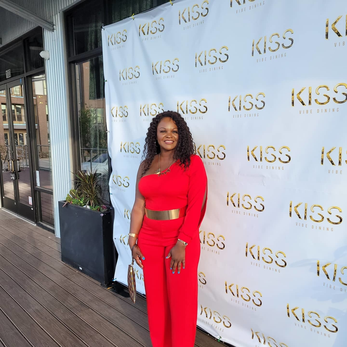 image of reviewer wearing the red one shoulder jumpsuit in front of a step-and-repeat