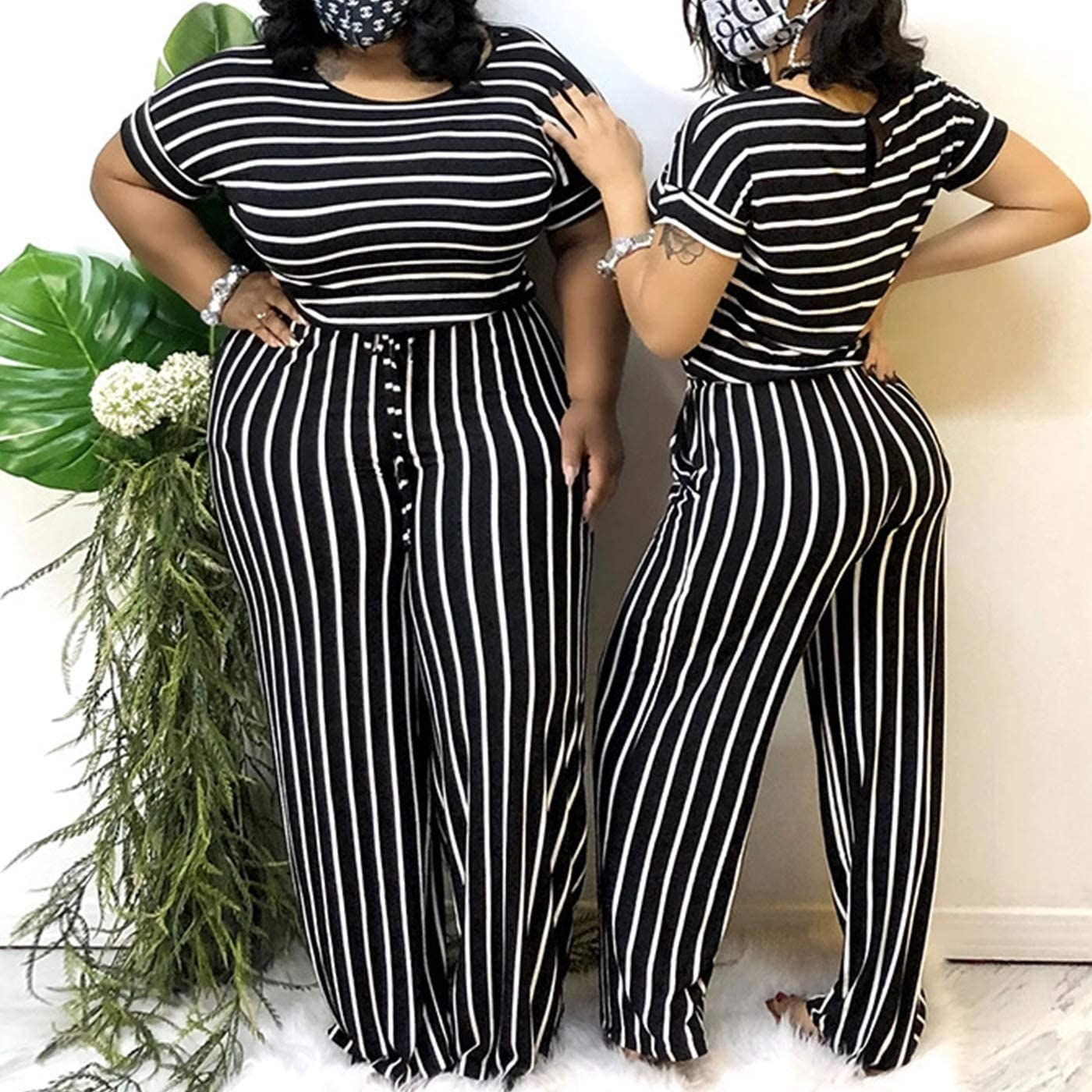 close up of two models wearing the black and white striped jumpsuit