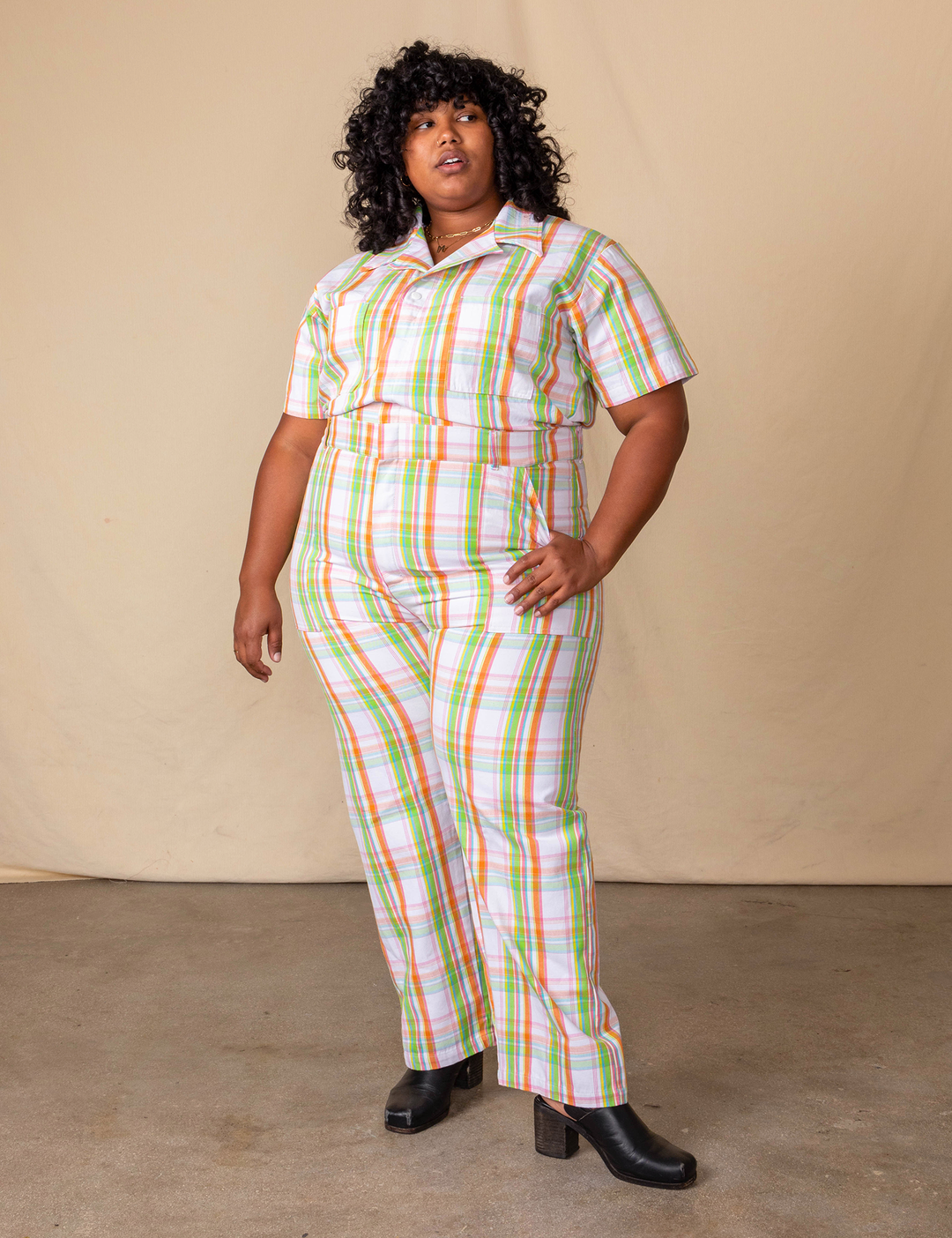a model wearing the rainbow plaid jumpsuit in a size 3XL