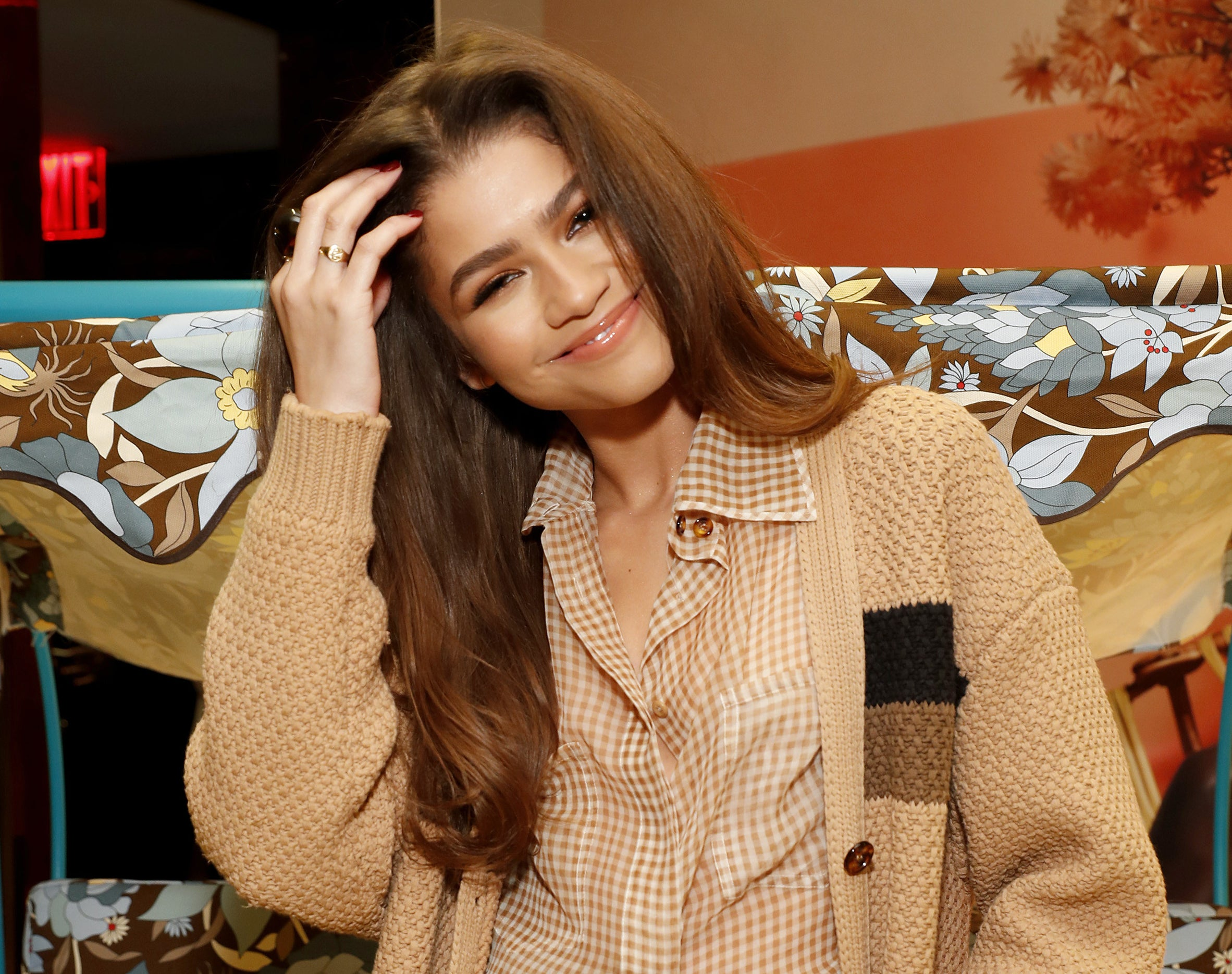 Zendaya smiles and poses while wearing a beige checked button down and beige cardigan