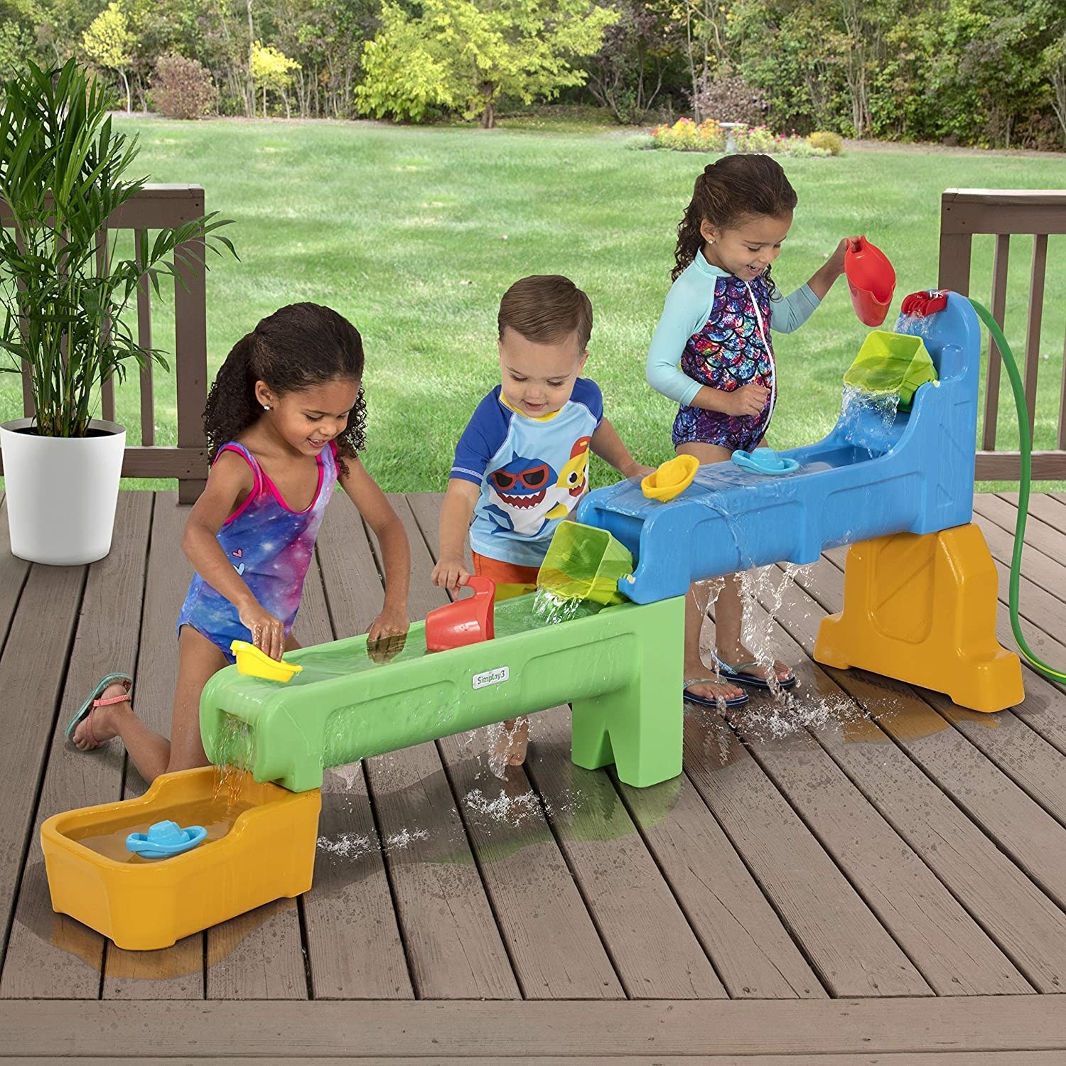 three kids playing on the water table