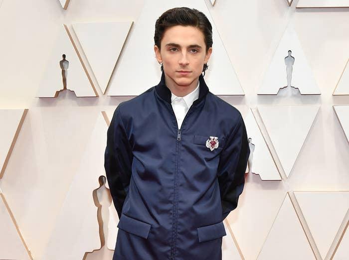 Timothée wears a navy nylon zip up jacket
