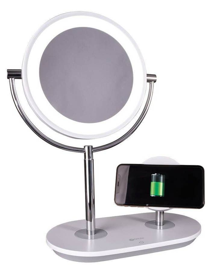 an LED mirror and wireless charger on a metal stand