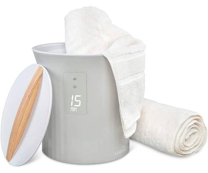 a gray towel warming machine with white lid and bamboo handle next to white towels