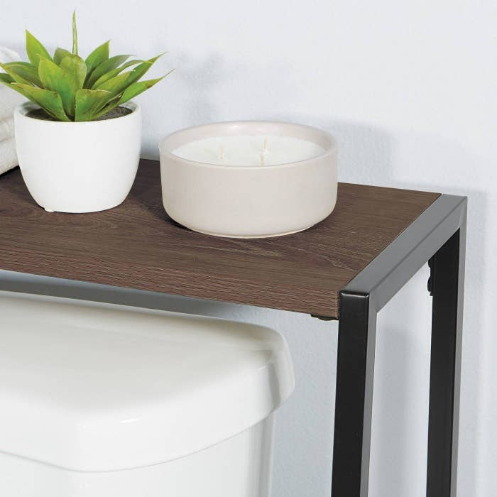 an over-the-toilet shelf with a candle and plant on top