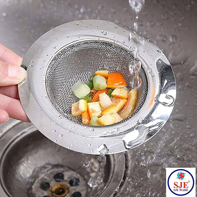 A person holding the sink strainer, it has filtered out residual vegetable bits