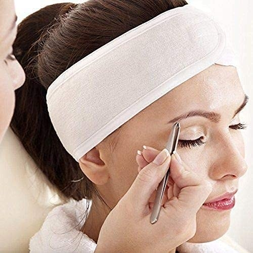 A person using the hair wrap while tweezing their brows