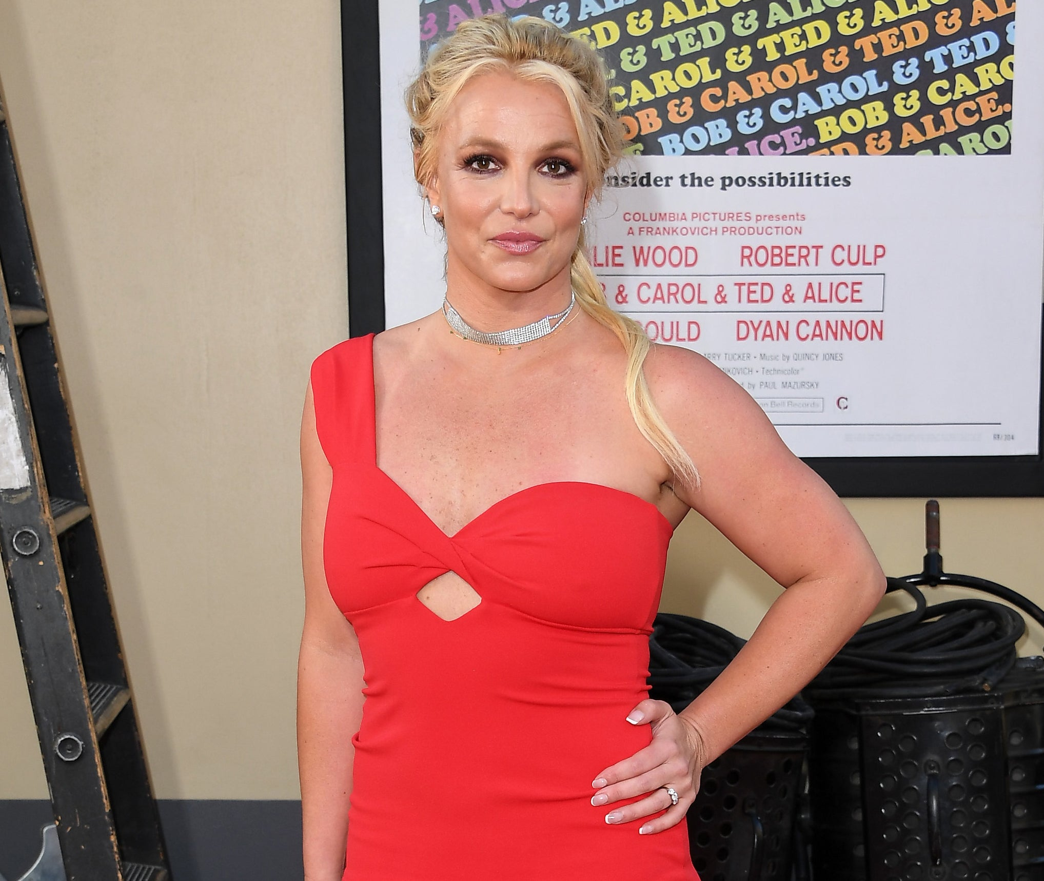 Britney wears a red one shoulder dress while posing at an event