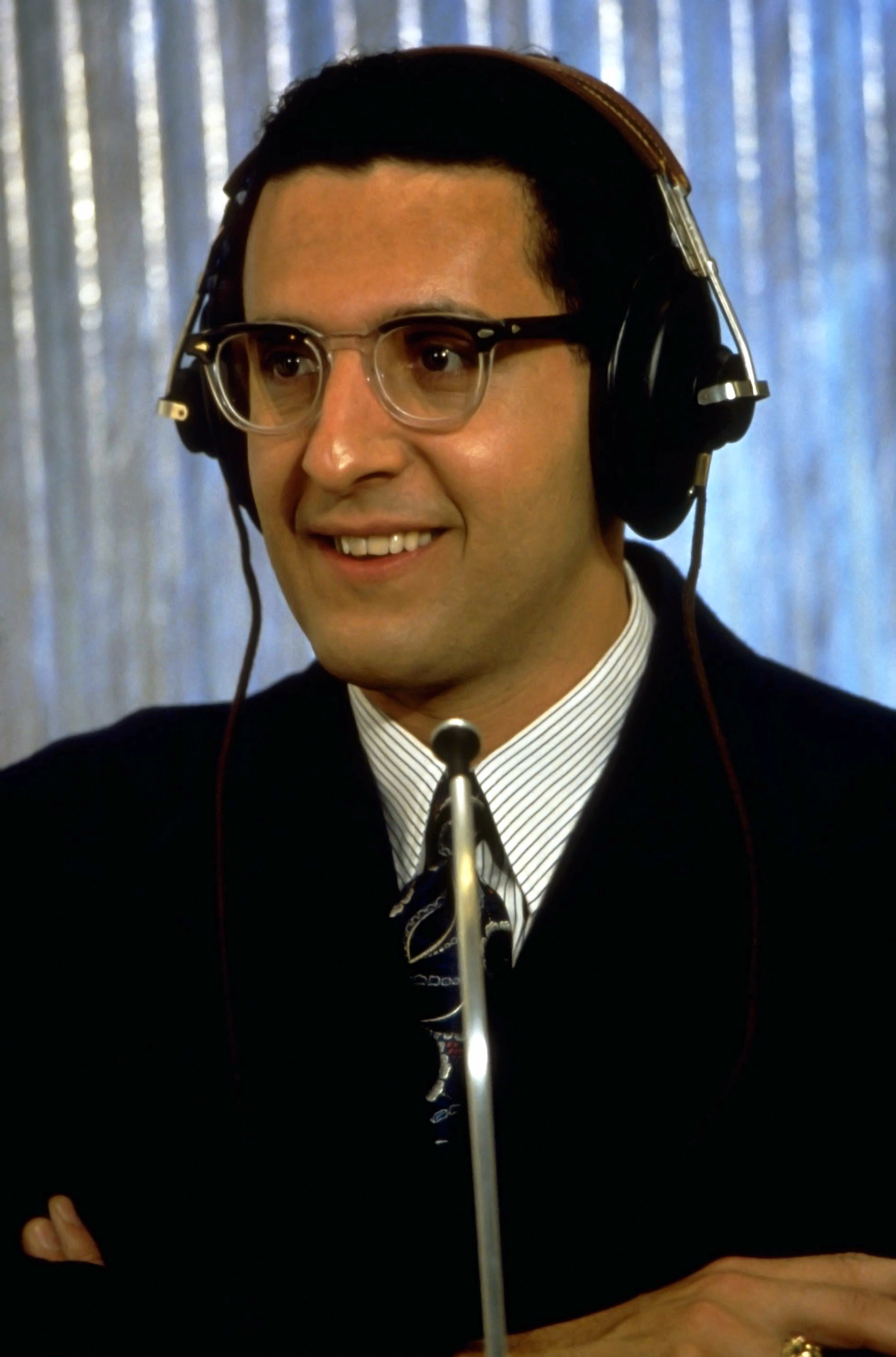 Turturro wearing a suit and headphones a contestant in the quiz show