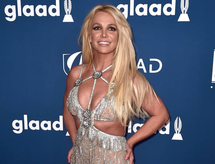 Britney poses with her hand on her hips and smiles