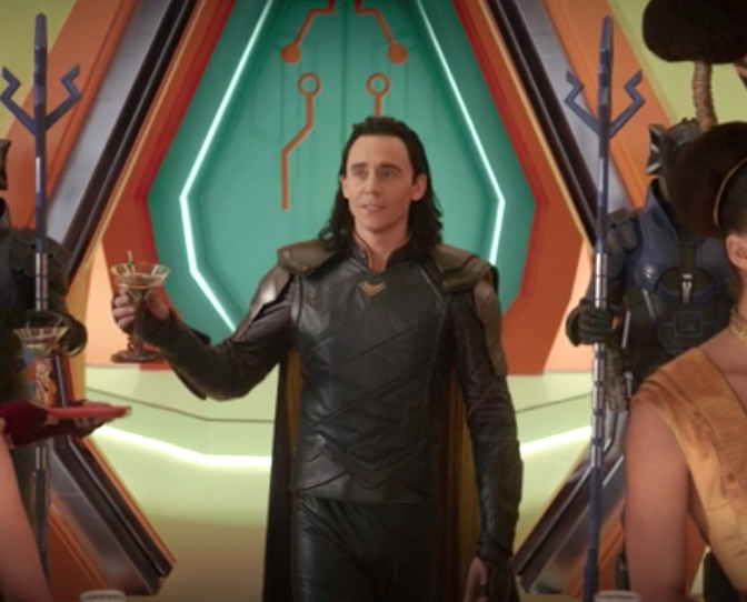 Loki holding a martini glass, wearing his blue and yellow outfit in Ragnarok