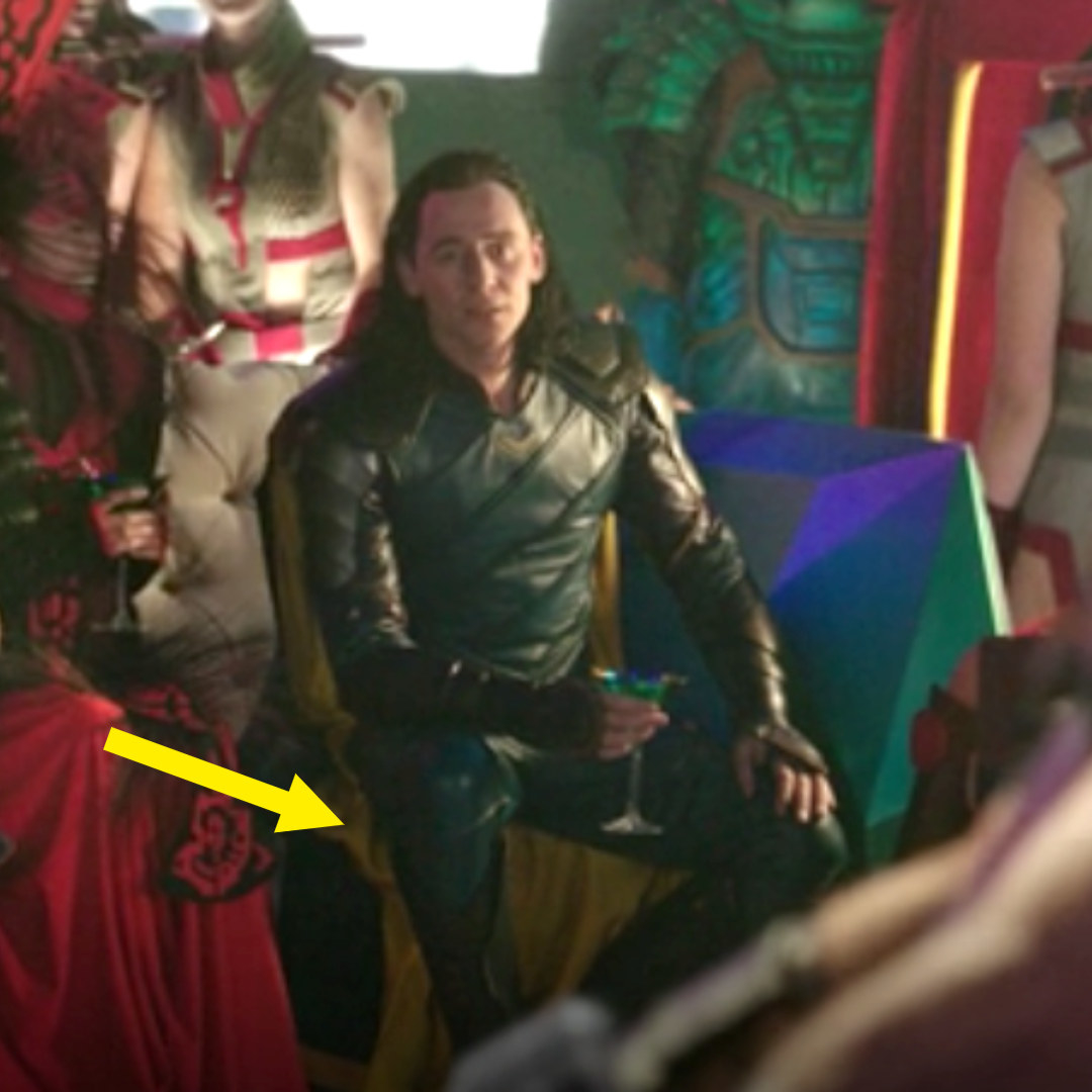 Loki sitting in the Grandmaster's palace, his cape showing bright yellow on the underside