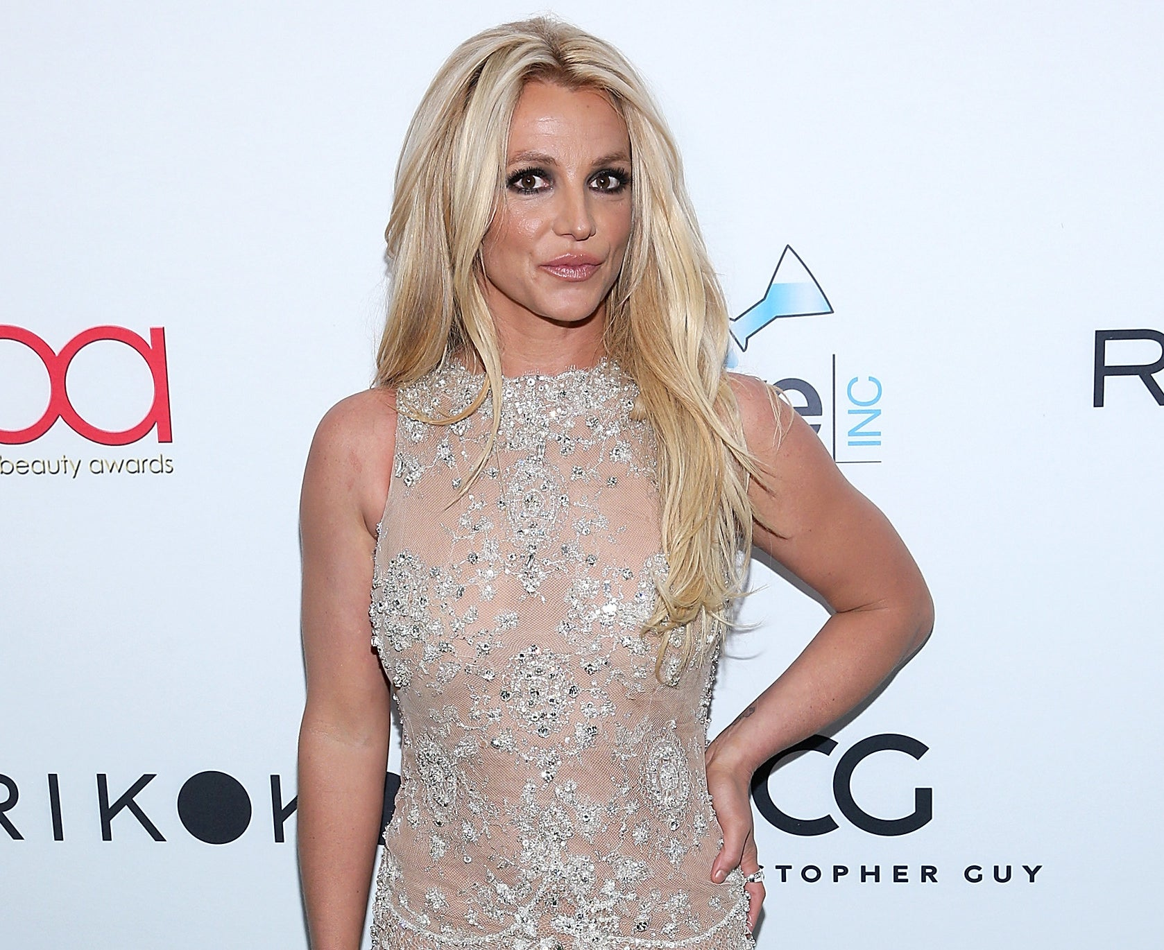 Britney smiles while posing in a beige crystal dress