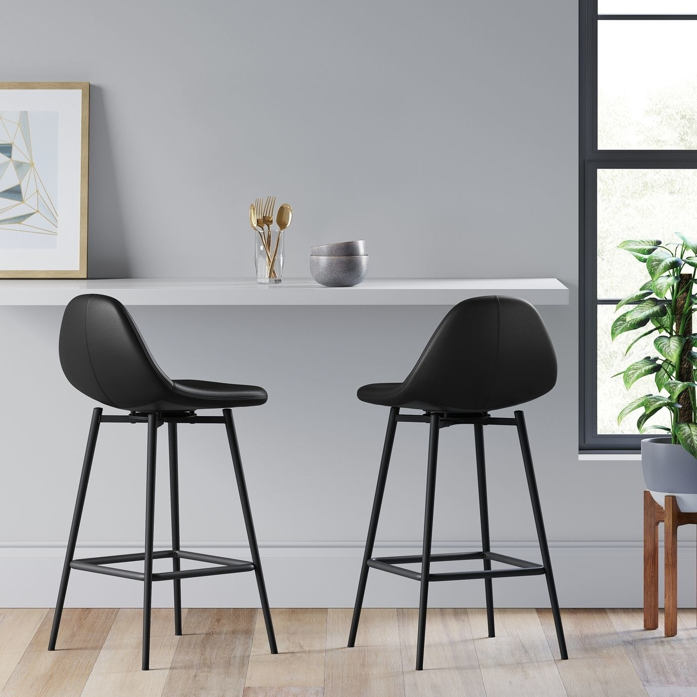 black faux leather counterstools with black legs