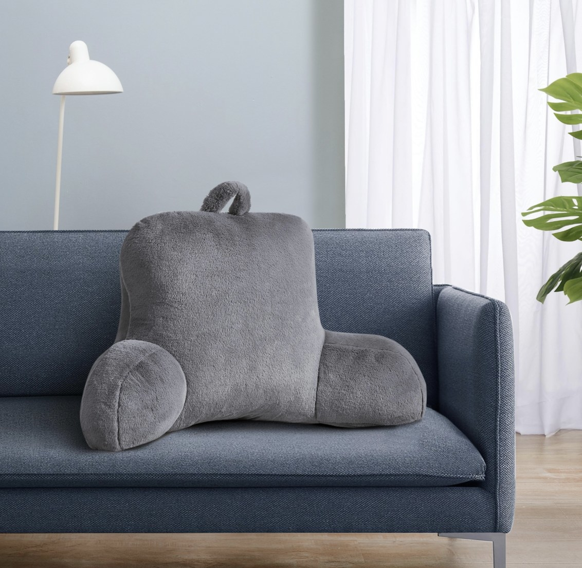 The grey plush pillow has two arms and a handle on the top