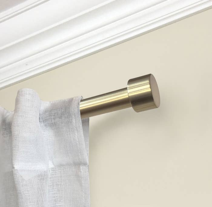 The gold rod has a cylindrical end and is holding up a white linen curtain