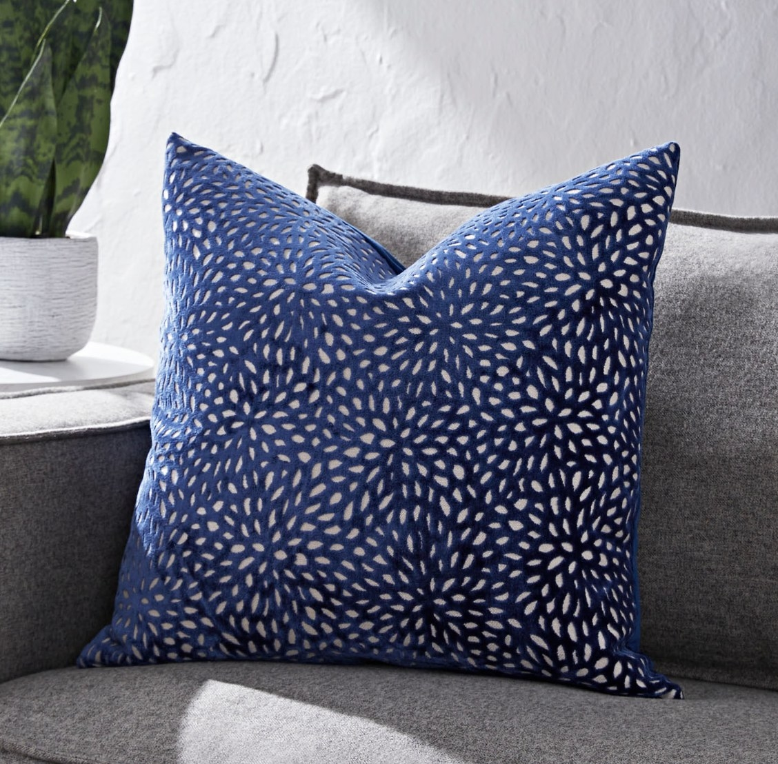 The blue velvet pillow has white cutouts that look like blooming flowers