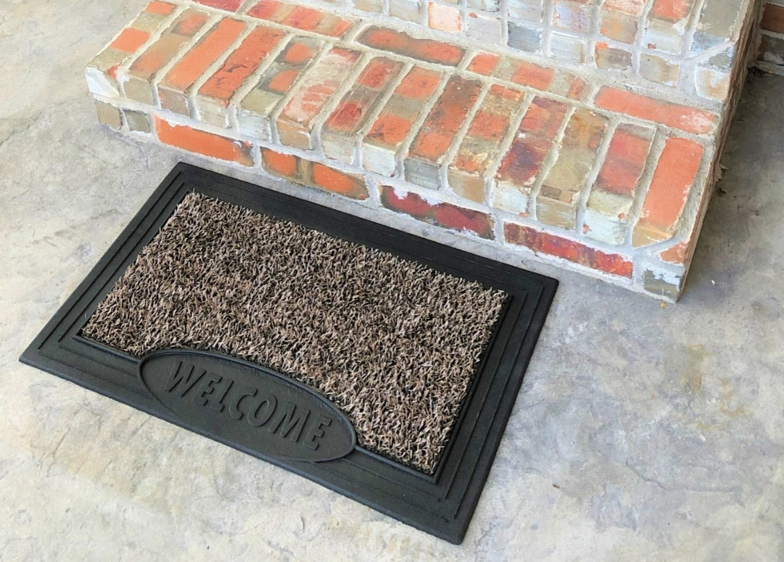 A welcome mat with black edges and a circular inset with the words WELCOME and a tan sandbar for scraping