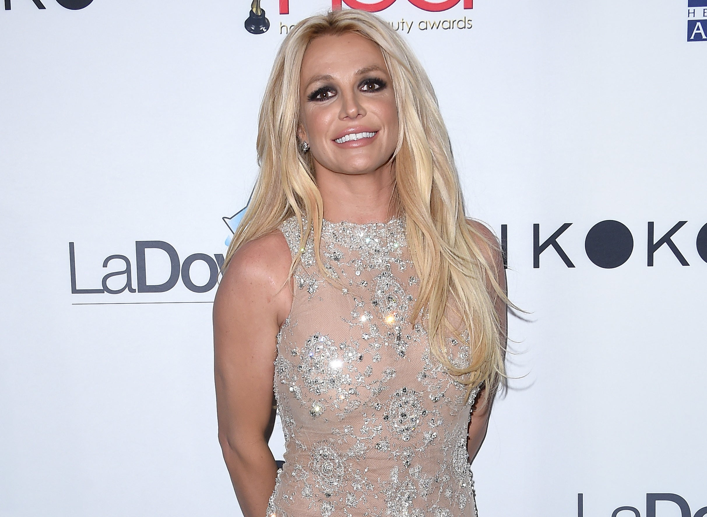 Britney smiles in a nude and crystal embellished dress