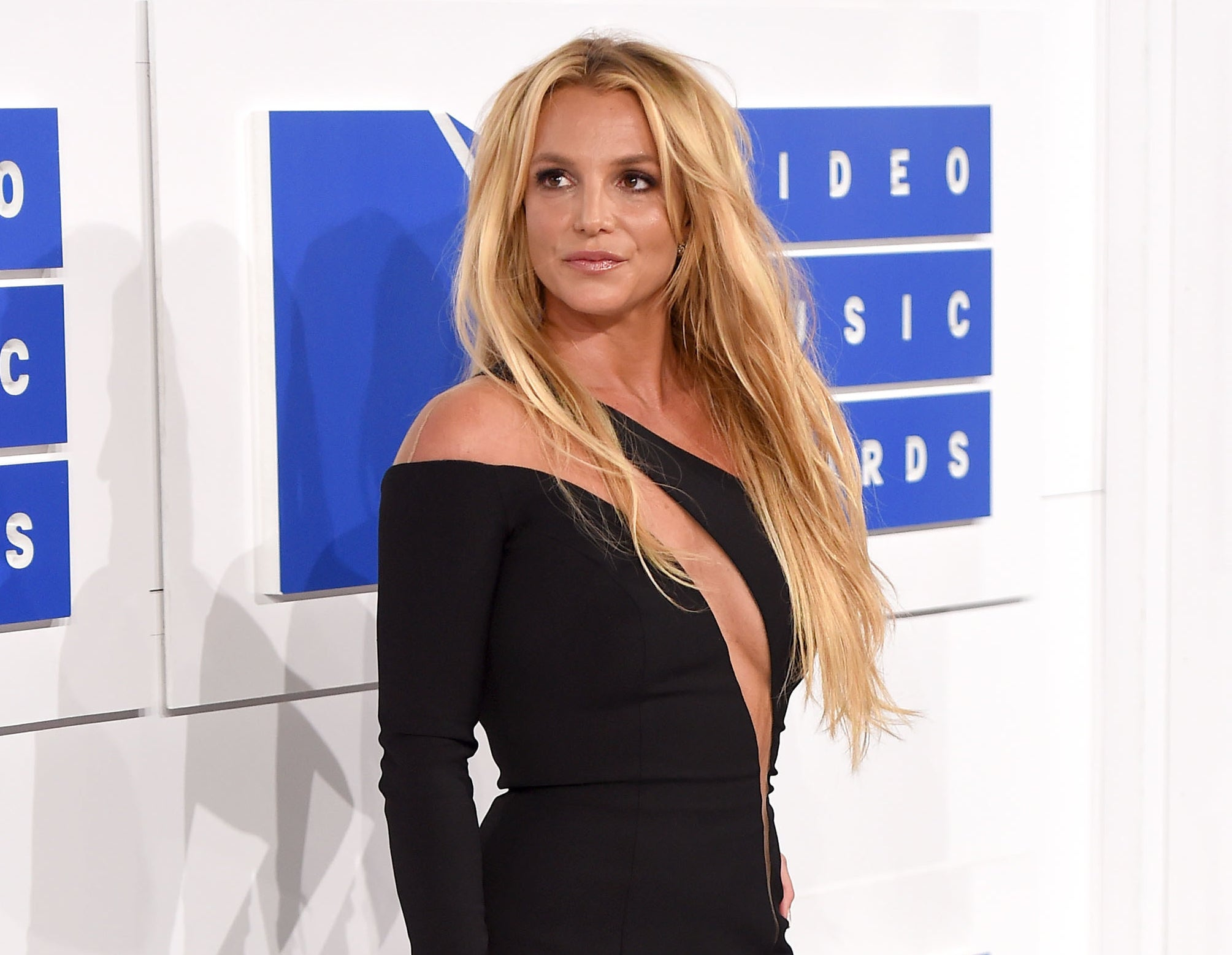 Britney softly smiles while looking off into the distance